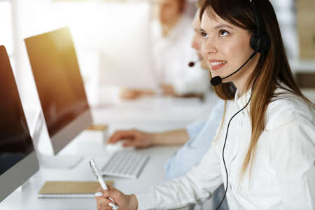 Foto de Asian woman working at customer service office. Business concept. Group of diverse operators at work in sunny call center. - Imagen libre de derechos