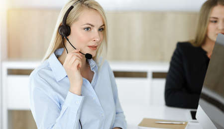 Photo for Blonde business woman sitting and communicated by headset in sunny call center office - Royalty Free Image