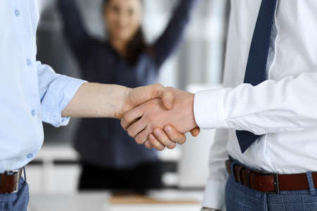 Foto de Two businessmen are shaking hands in office, close-up. Happy and excited business woman stands with raising hands at the background. Business people concept - Imagen libre de derechos