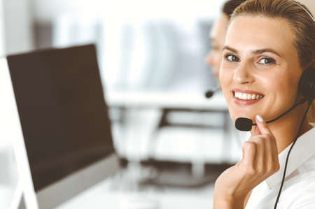Photo for Blond female customer service representative and her colleague are consulting clients online using headset. Call center and business people concept - Royalty Free Image