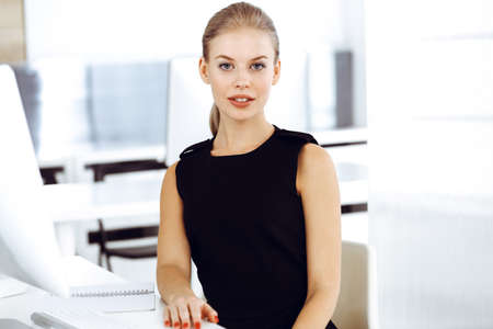 Photo pour Young blond businesswoman working on computer while sitting at the desk in modern office. Business people concept. Black dress do suits to her much at this portrait - image libre de droit
