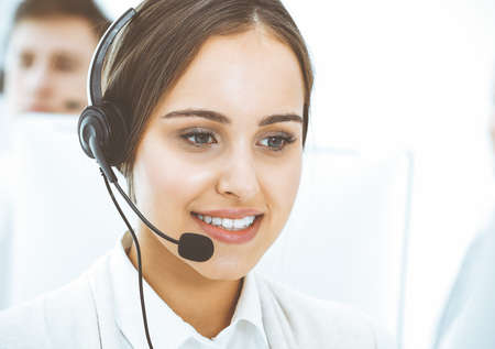 Photo pour Call center. Group of diverse operators at work. Beautiful woman in headset communicating with customers of telemarketing service. Business concept - image libre de droit