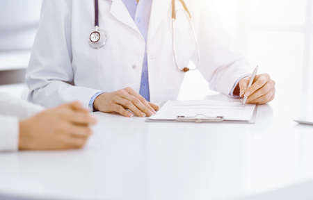 Photo pour Unknown woman-doctor and female patient sitting and talking at medical examination in sunny clinic, close-up. Medicine concept - image libre de droit