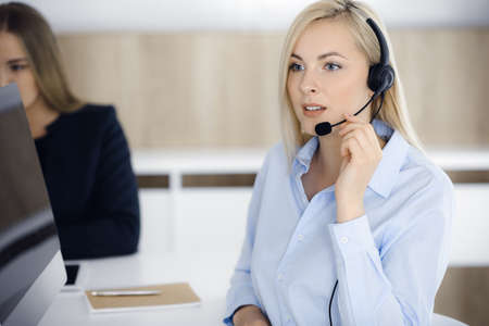Photo for Blonde business woman sitting and communicated by headset in call center office. Concept of telesales business - Royalty Free Image