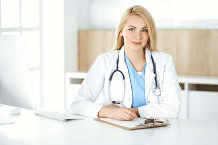 Photo pour Woman-doctor at work while sitting at the desk in hospital or clinic. Blonde cheerful physician filling up medication history record form - image libre de droit