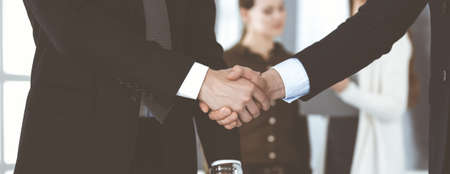 Foto für Business people shaking hands after contract signing while standing in a modern office. Teamwork and handshake concept - Lizenzfreies Bild