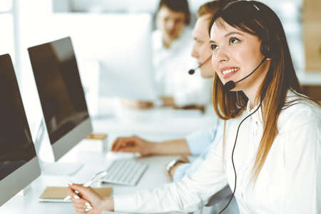 Photo pour Group of diverse operators at work in call center. Beautiful asian woman sitting in headset at customer service office. Business concept - image libre de droit