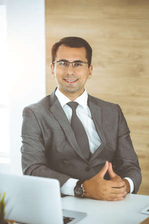 Photo pour Cheerful smiling businessman sitting at a desk in sunny office. Business concept - image libre de droit