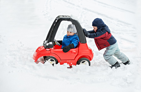 A young boy dressed for cold weather sits in a red toy car stuck in the snow during the winter season.  His older brother helps by giving the car a push from behind.