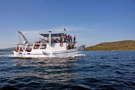 Photo pour Betina, Croatia - 15 August, 2011: Tourist motor boat Rom full of tourists during the regatta Latin Sail - image libre de droit