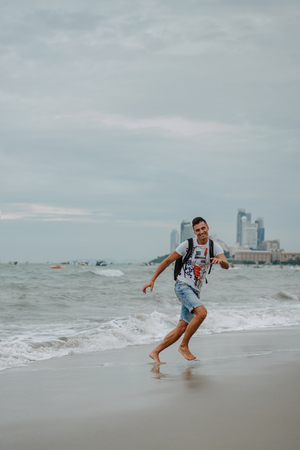 Photo for Young man enjoying his vacation on the ocean coast. Running, jumping and having fun at the seaside. Fun on the ocean. Evening Pattaya, Thailand. - Royalty Free Image