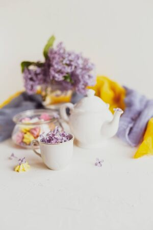 Photo pour Purple spring lilac flowers still life on white background in the morning. Tea-time or breakfast with black tea and candies. - image libre de droit