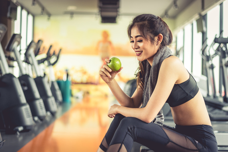Foto de Asian woman holding and looking green apple to eat with sports equipment and treadmill in background. Clean food and Healthy concept. Fitness workout and running theme. - Imagen libre de derechos