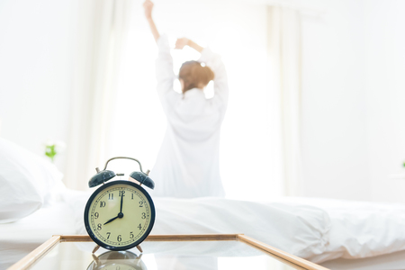 Foto de Back view of woman stretching in morning after waking up on bed near window with alarm clock. Holiday and Relax concept. Lazy day and Working day concept. Office woman and worker in daily life theme - Imagen libre de derechos