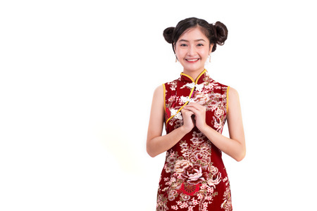 Foto de Young Asian beauty woman wearing cheongsam and blessing or greeting gesture in Chinese new year festival event on isolated white background. Holiday and Lifestyle concept. Qipao dress wearing - Imagen libre de derechos