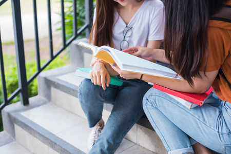 Close up of two Asian beauty girls reading and tutoring books for final examination together. Student smiling and sitting on stair. Education and Back to school concept. Lifestyles and People theme.