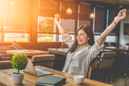 Foto de Beauty Asian woman raising two hands after finishing job happily with laptop computer. People and lifestyles concept. Technology and Business working theme. Occupation and coffee shop theme. - Imagen libre de derechos