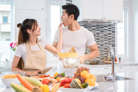 Foto de Asian couples feeding food together in kitchen. People and lifestyles concept. Sweet honeymoon and Holidays concept. Valentines day and wedding theme. Puppy love and romantic theme. - Imagen libre de derechos