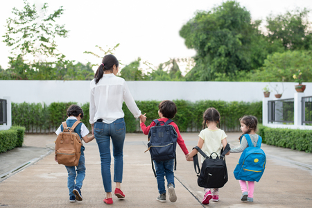 Photo pour Group of preschool student and teacher holding hands and walking to home. Mom bring her children go to school together. Back to school and Education concept. People and lifestyles theme. Back view - image libre de droit
