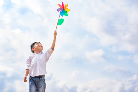Photo pour Boy holding colorful pinwheel in windy at outdoors. Children portrait and kids playing theme. - image libre de droit
