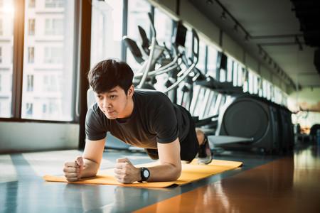 Foto de Portrait of Asian fitness man doing planking exercise in gym. People lifestyle and Sport workouts concept. - Imagen libre de derechos