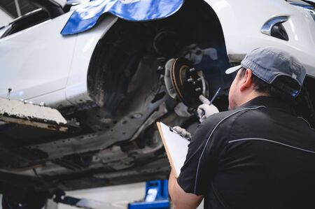Photo pour Asian male car technician car maintenance for customers according to specified vehicle maintenance checklist. Disk brake pad wear automotive repairing on vehicle. Safety inspection check service - image libre de droit