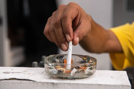 Photo pour Hand putting out cigarette and destroy in ashtray at outdoor in front of house. Healthy and people concept. World No Tobacco Day theme - image libre de droit