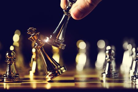 Photo pour Closeup king chess piece defeated enemy or trade competitor by checkmate at end of chessboard game. Businessman moving chess to success competition by hand. Leadership and strategy management - image libre de droit