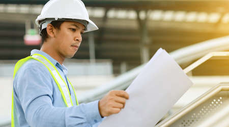 Photo pour engineer hold blueprint draft paper at construction site - image libre de droit