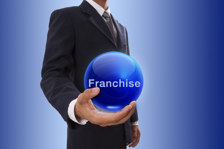 Businessman hand holding blue crystal ball with franchise word.