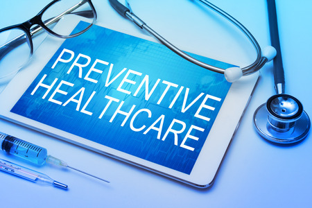Preventive healthcare word on tablet screen with medical equipment on background