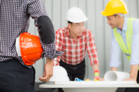 Photo for engineer and construction team wearing safety helmet and looking blueprint on the table. they are working on checking progress of construction site. engineer and client reviewing material and checking construction process in construction site area. - Royalty Free Image