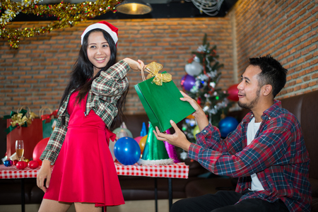 handsome man sent green gift bag to beautiful woman, who wear red dress and santa claus hat at the party. concept of Christmas party and New year party.