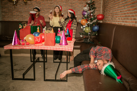 picture of Asian man are very drunk and sleeping on the sofa with his friend are drinking champagne at the party. concept of Xmas party, Christmas party and New year party celebration.