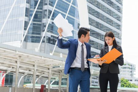 Photo pour Angry businessman stand and holding document on hand, he blaming secretary for work mistakes. - image libre de droit