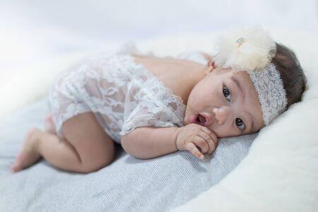 Photo pour adorable little baby with white ctrue dress poses for a photo shoot. - image libre de droit