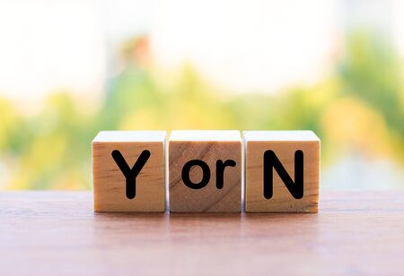 The saving of words on a wooden cube. The letters y and n represent the question of whether yes or no.