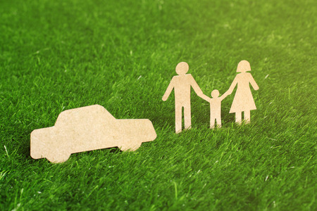 Family made from cut-out recycle paper on grass