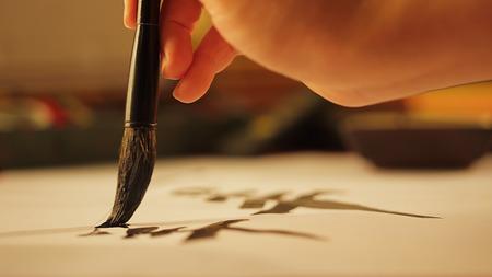 Foto de Close up on hand holding brush writing calligraphy - Imagen libre de derechos