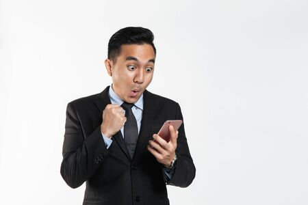 Photo pour Man in suit with surprise expression while looking at his phone - image libre de droit