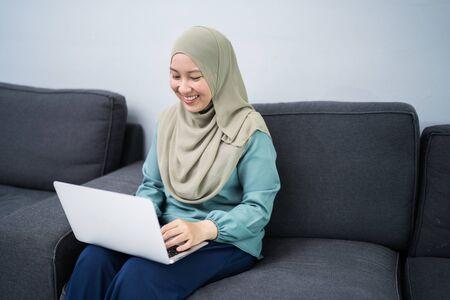 Photo pour Female muslim using laptop at home environment. - image libre de droit