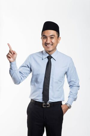 Photo pour Asian business man in suit and songkok pointing his hands - image libre de droit