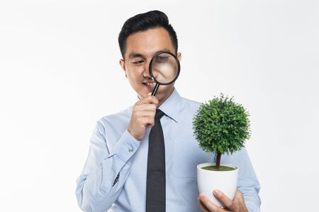 Photo pour Man in office wear holding a potted plant while magnifying on it - image libre de droit