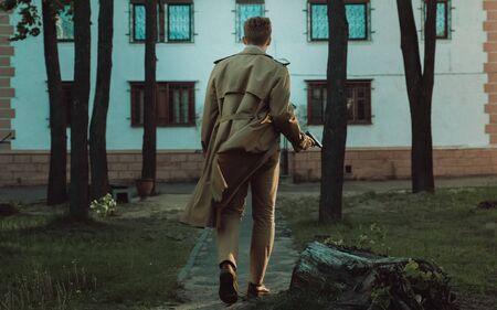 Photo pour Film noir Detective man in a raincoat in a dangerous with a gun in his hand walking along the road to the building - image libre de droit