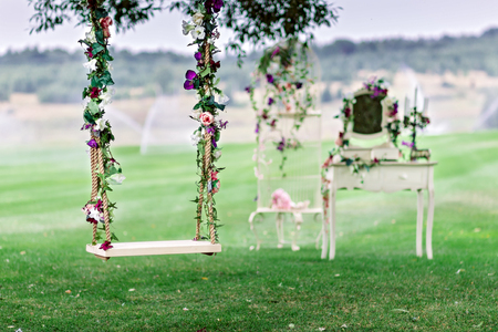 Foto de Wedding swing decorated with flowers hanging on the branches of the old willow - Imagen libre de derechos