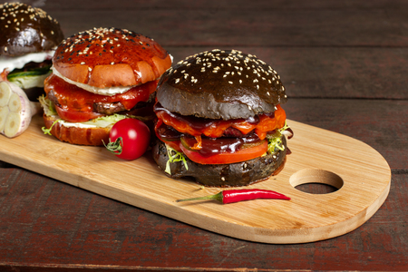 Photo for Four burgers on a light wooden board surface. Clouse-up. - Royalty Free Image