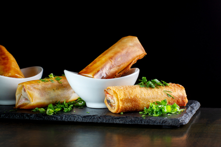 Photo pour Fried spring rolls on black slate decorated with greens. - image libre de droit
