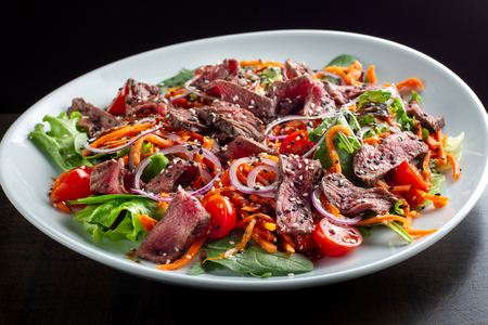 Photo pour Beef salad sprinkled with sesame and garnished with onion rings. - image libre de droit