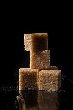 Pyramid of brown sugar cubes on a dark background.