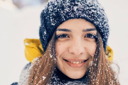 Photo pour Winter portrait of young beautiful woman wearing knitted snood covered in snow. Snowing winter beauty fashion concept - image libre de droit